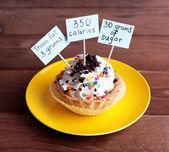 Fotografie Lahodný dort s kalorií počet štítků na barevné desky na dřevěný stůl pozadí
