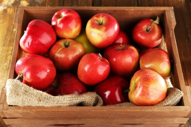 Red apples in wooden crate with burlap cloth