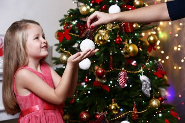 Little girl taking bauble near Christmas tree on white wall background