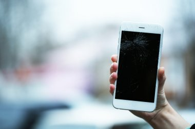 Broken iPhone on hand outdoors