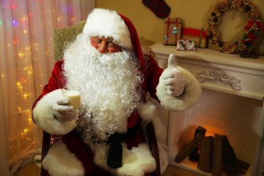 Santa Claus sitting with milk glass in comfortable chair near fireplace at home