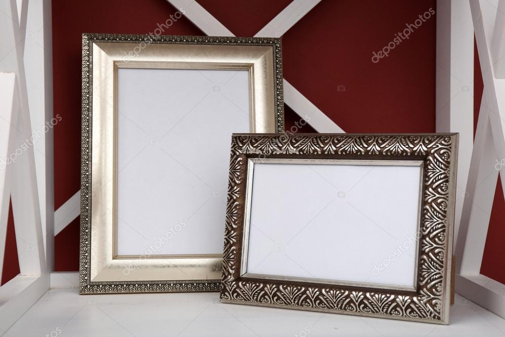 Dos marcos en el estante, sobre fondo de pared color de la foto ...