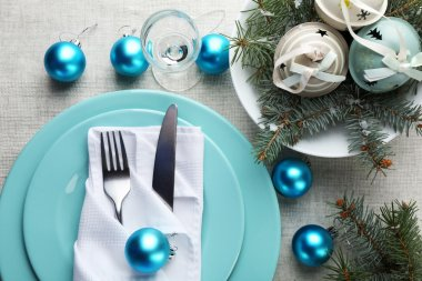 Stylish blue and white Christmas table setting on grey tablecloth background