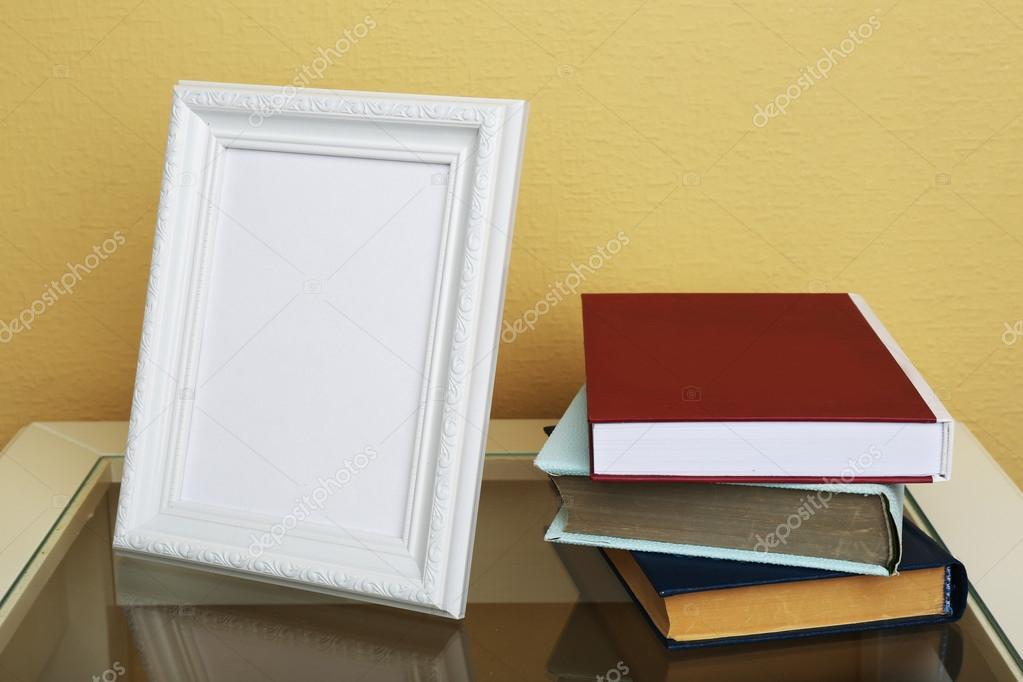 Marco de fotos con libros sobre la mesa de café sobre fondo de papel ...