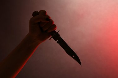 Female hand holding knife on red background