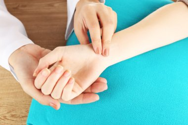 Checking pulse by hand on wooden table background