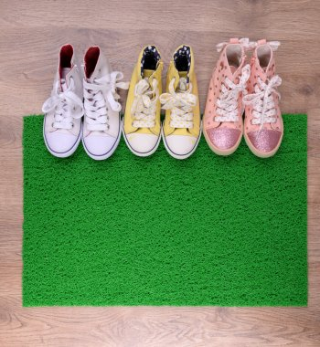 Green carpet on floor and converse close-up