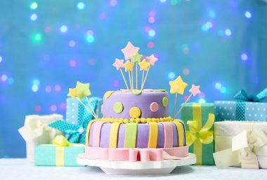 Delicious birthday cake on shiny blue background