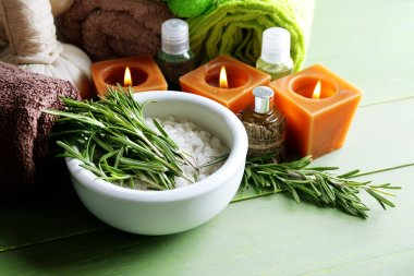 Branches of rosemary and sea salt in bowl, towels, candles and bottle with massage oil on wooden background. Rosemary spa concept