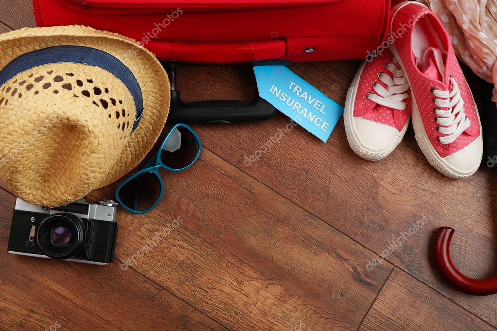 Suitcase and tourist stuff with inscription travel insurance on wooden background