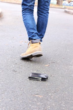 Lost leather wallet and walking male legs, outdoors