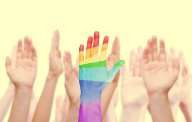 Man's hands painted as the rainbow flag on other hands background isolated on white
