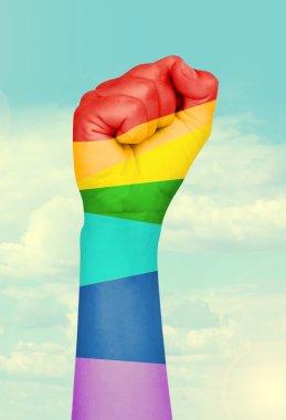 Man's hand painted as the rainbow flag on sky background