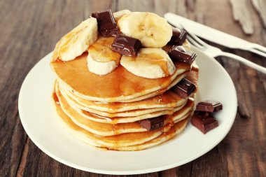 Stack of delicious pancakes with chocolate, honey and slices of banana on plate on wooden table background
