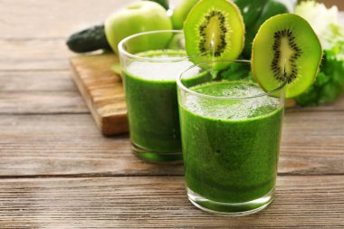 Green fresh healthy juice with fruits and vegetables on cutting board and wooden table background
