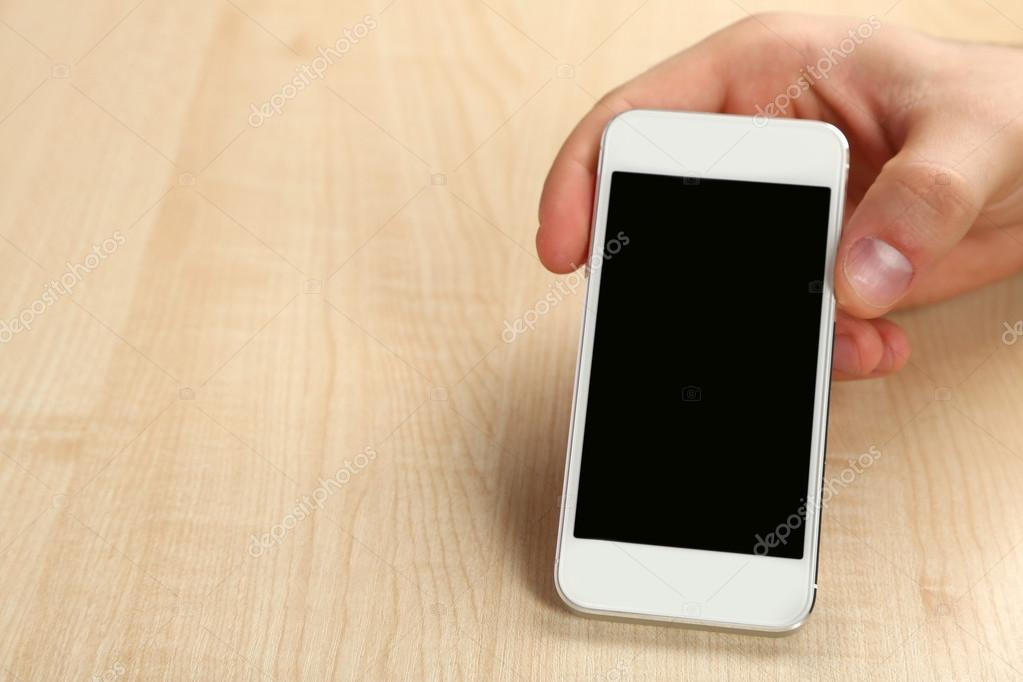 Hand Holding Smart Mobile Phone On Wooden Table Background Stock