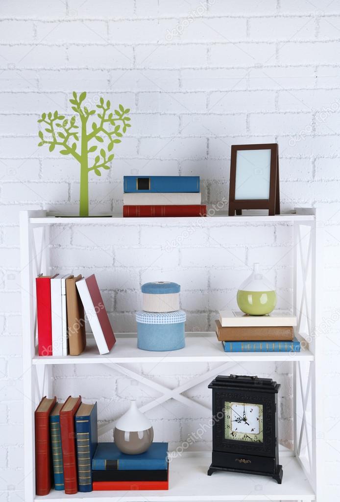 Boekenkasten met boeken en decoratieve objecten op bakstenen muur ...