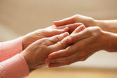 Vecchi e giovani che tengono le mani