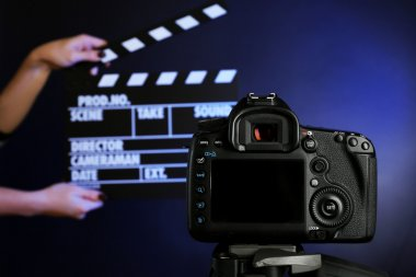 Hands with movie clapper board in front of camera on dark background