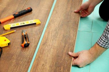 Carpenter worker installing laminate flooring in the room