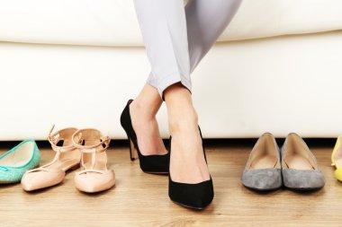 Trying on shoes by elegant lady sitting on white sofa background