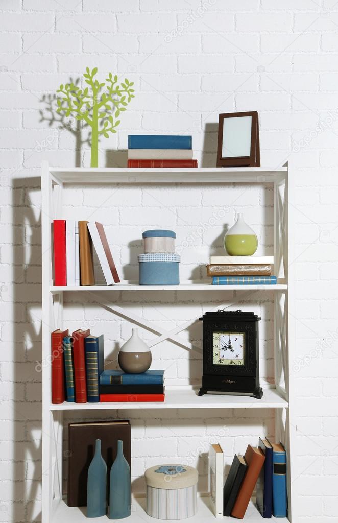 boekenkasten met boeken en decoratieve objecten op bakstenen muur achtergrond foto van belchonock