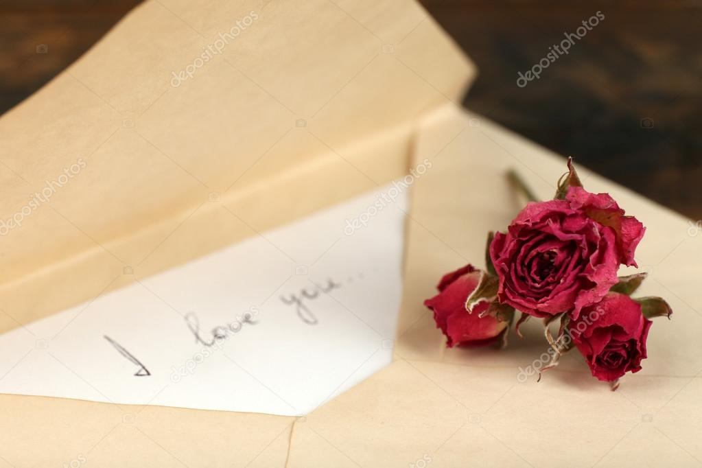 envelope with love letter and dried rose on rustic wooden table background stock photo