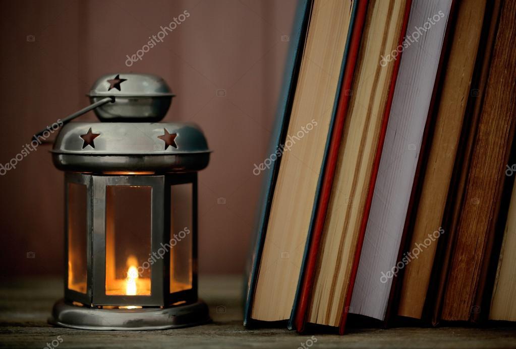 Dekorative Bücher bücher und dekorative laterne auf tisch und holzbohlen hintergrund