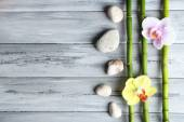 Fotografie Orchid flowers  and bamboo with pile stones on wooden background