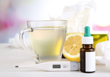 Hot tea for colds, pills and handkerchiefs on table on bright background