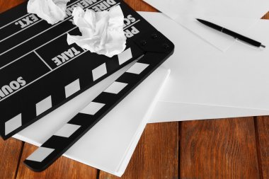 Moving clapper with sheets of paper and pen on wooden planks background