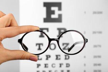 Glasses in hands on eye chart