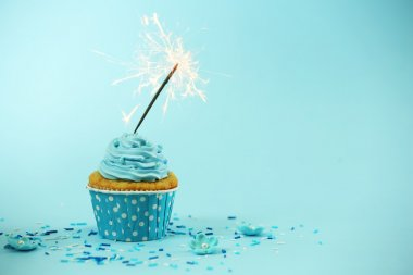 Cupcake with sparkler on blue background