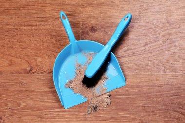 Trash in scoop on floor close-up