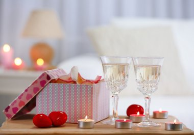 Champagne glasses, gift box and rose petals for celebrating Valentines Day