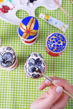 Young woman painting Easter eggs on table close up