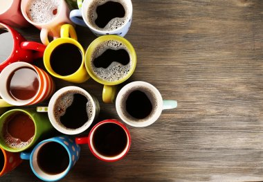 Many cups of coffee on wooden background