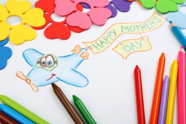 Happy Mothers Day message written on paper with pencils and decorative flowers close up