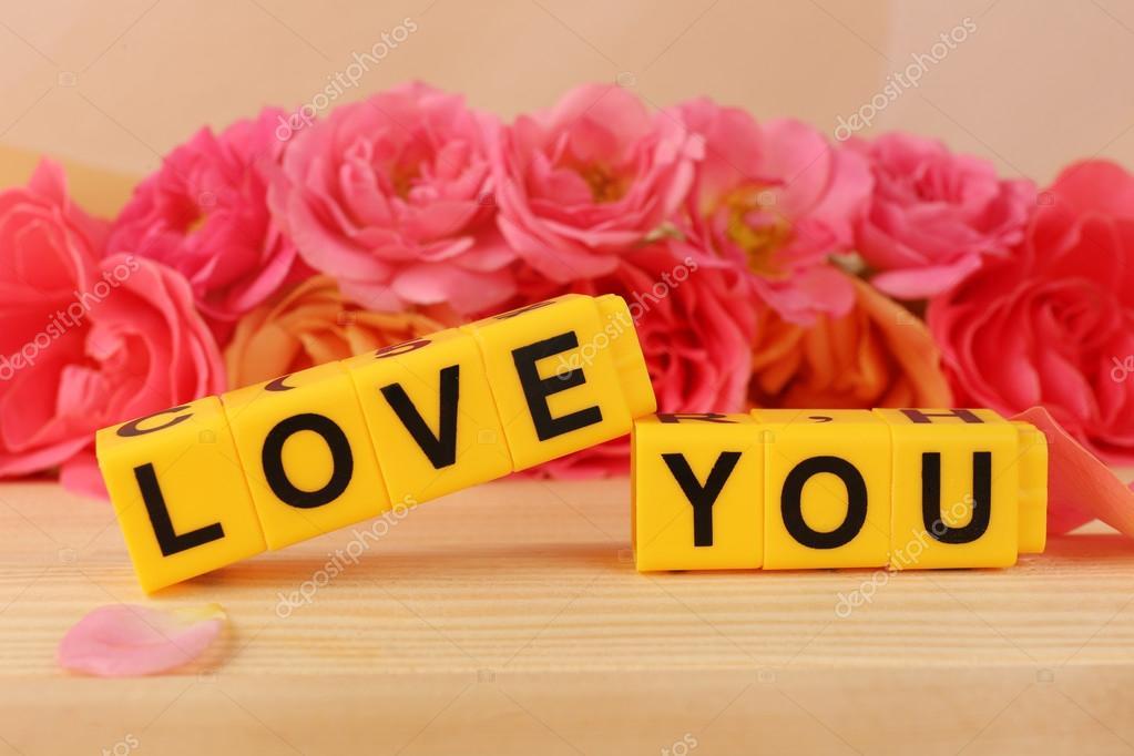Woorden love you gevormd uit kubussen met bloemen op lichte woorden love you gevormd uit kubussen met bloemen op lichte achtergrond stockfoto voltagebd Choice Image