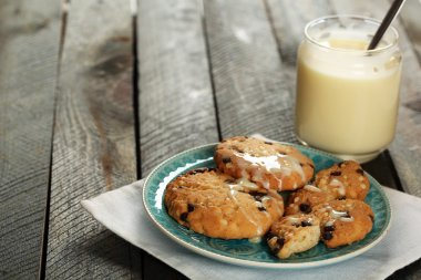 Cookies on plate with jar of condensed milk on wooden background