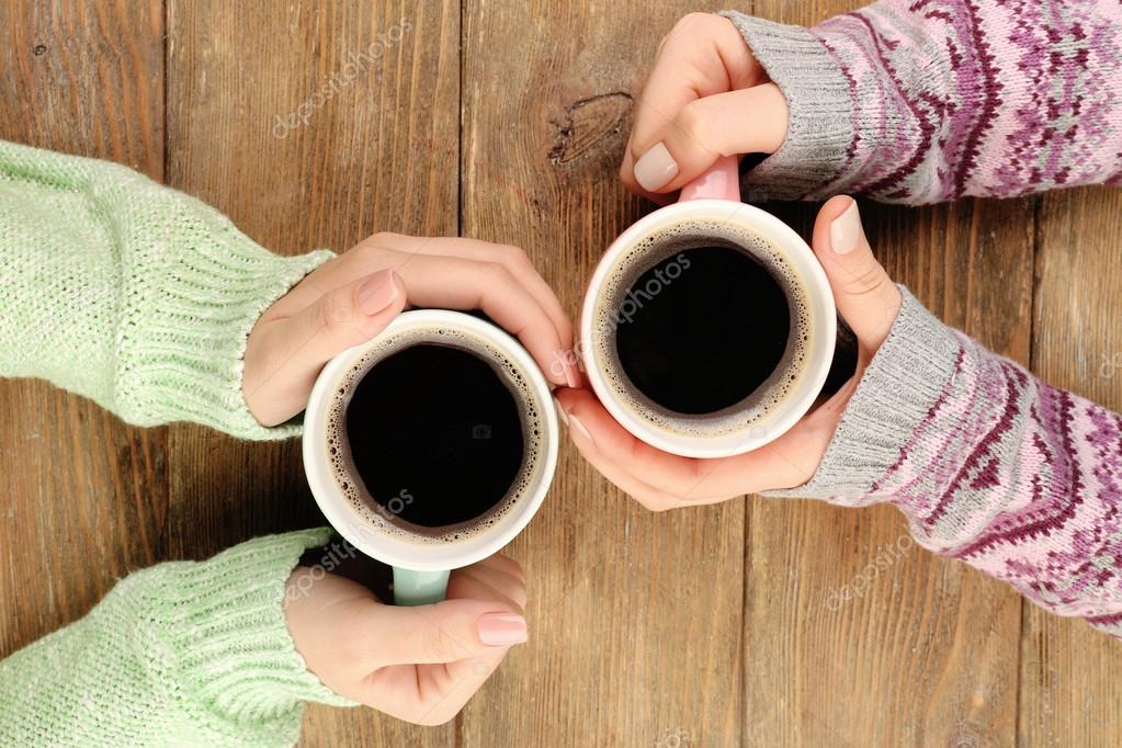 Female hands holding cups of coffee on rustic wooden table ...