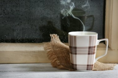 Cup of hot drink with napkin on windowsill on rain background