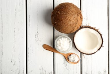 Coconut with coconut oil in jar on wooden background