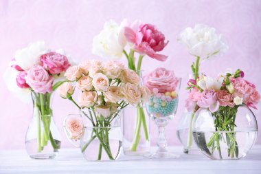Beautiful spring flowers in glass vases on light pink background