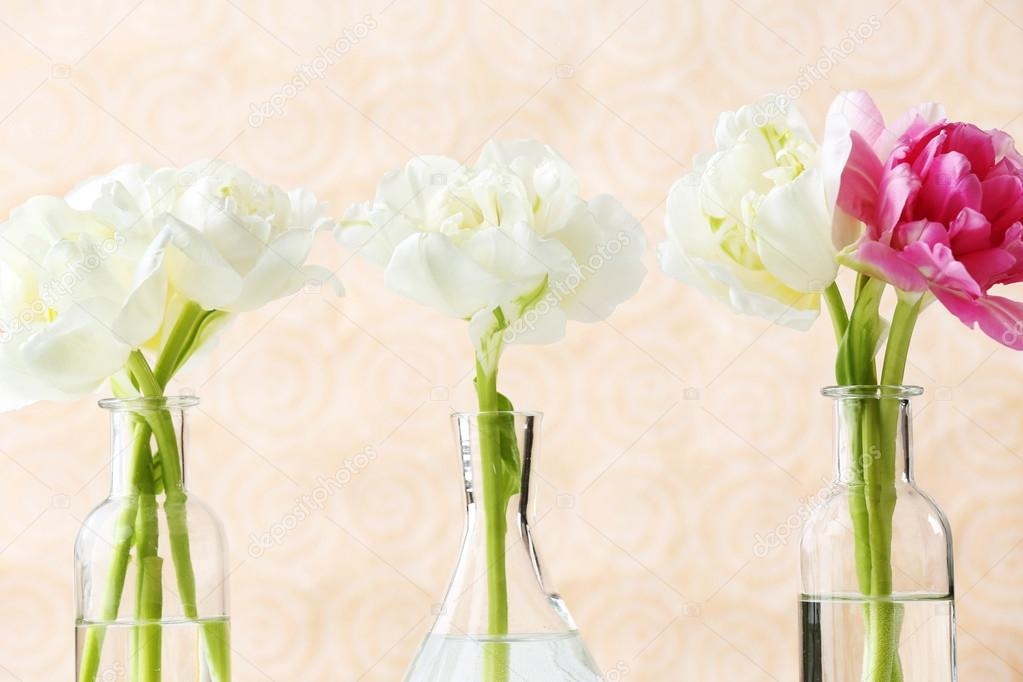 Beautiful Tulips In Glass Vases On Light Color Background Stock