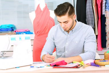 Young man fashion designer creates new collection of clothes