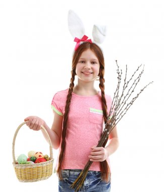Beautiful little girl holding wicker basket with Easter eggs and pussy-willow branches, isolated on white