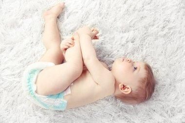 Cute baby boy on carpet, on light background