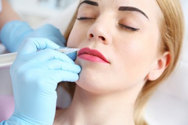 Cosmetologist applying permanent make up on lips