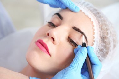 Cosmetologist applying permanent make up on eyebrows